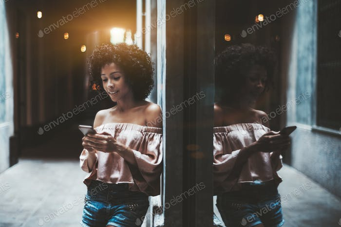 Biracial girl with cellphone, street