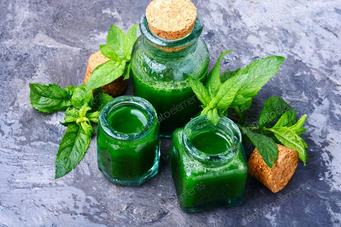 Essential mint oil with green leaves