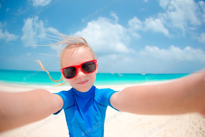 Adorable little girl making selfie at tropical white beach