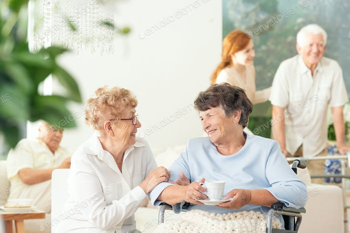Front view of two happy geriatric women talking and holding hand