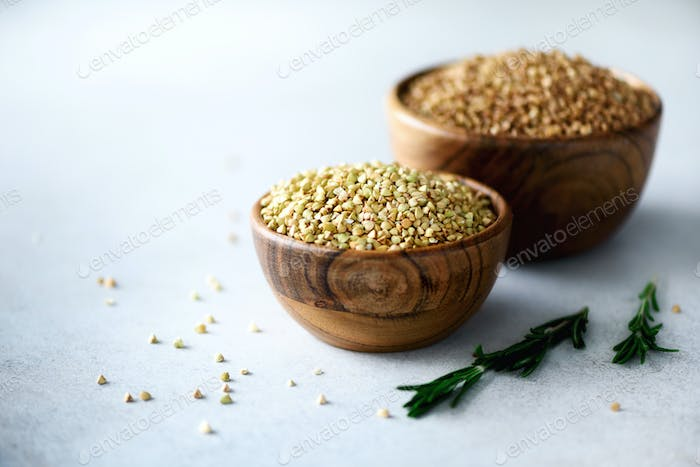 Raw organic green and roasted buckwheat in wooden bowls and rosemary on grey background. Copy space