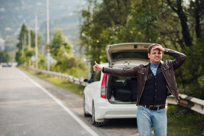 Hitchhiking - Need a drive. Young man on the road with his hand raised in front of car