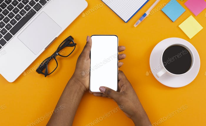 Black woman using smartphone with blank screen at workplace