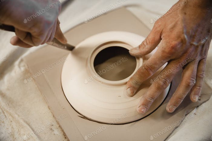 Potter master cutting the clay