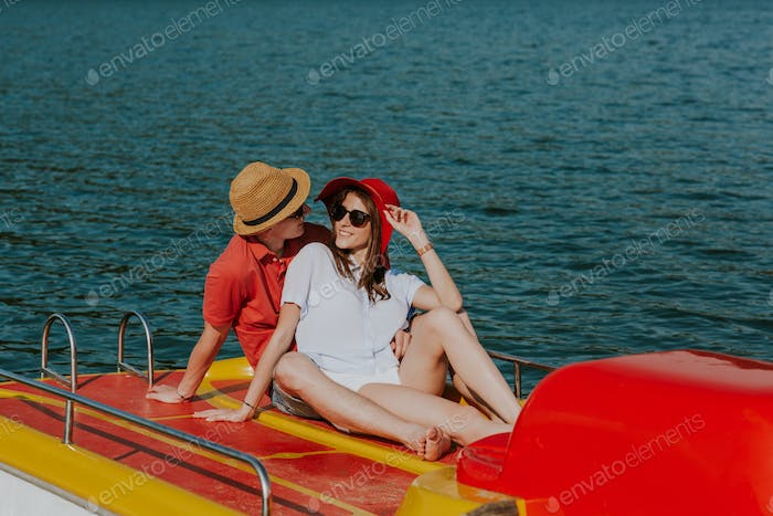 Cheerful man and woman cuddling while boating.