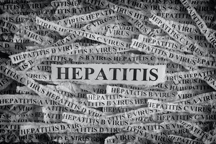 Torn pieces of paper with the words Hepatitis