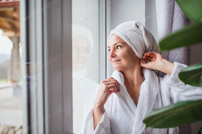Portrait of woman with bathrobe and towel on head standing indoors