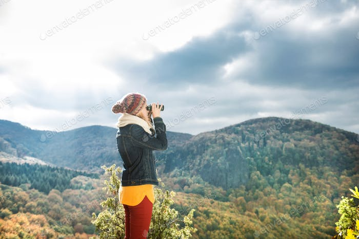 Beautiful woman looking through binoculars, colorful sunny autumn forest