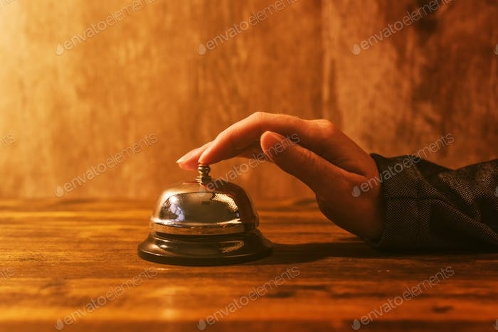 Businesswoman ringing hotel reception bell
