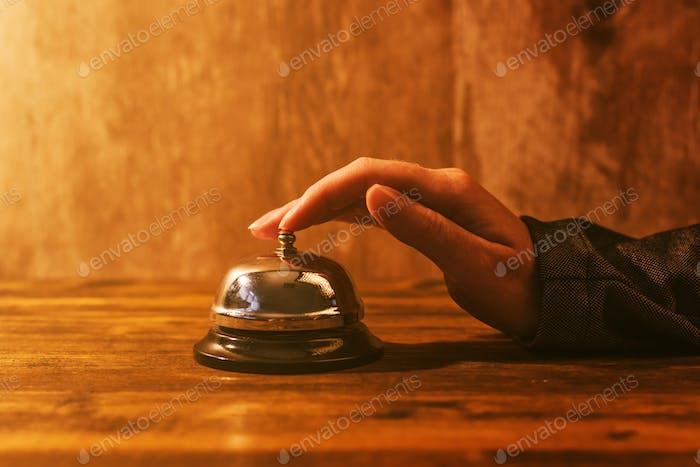 Geschäftsfrau klingelt Hotelrezeption Glocke