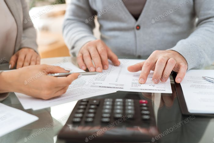 Hands of agent and senior client discussing investment information in paper
