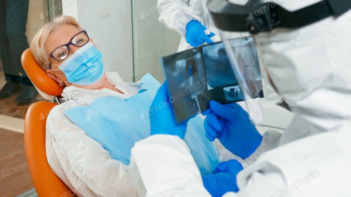 Doctor with face shield reviewing panoramic dental x-ray image