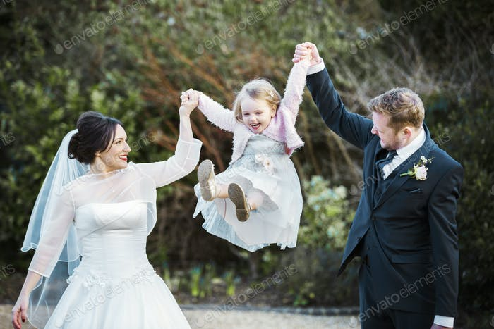 A bride and bridegroom, a couple on their wedding day holding and swinging a little girl in the air