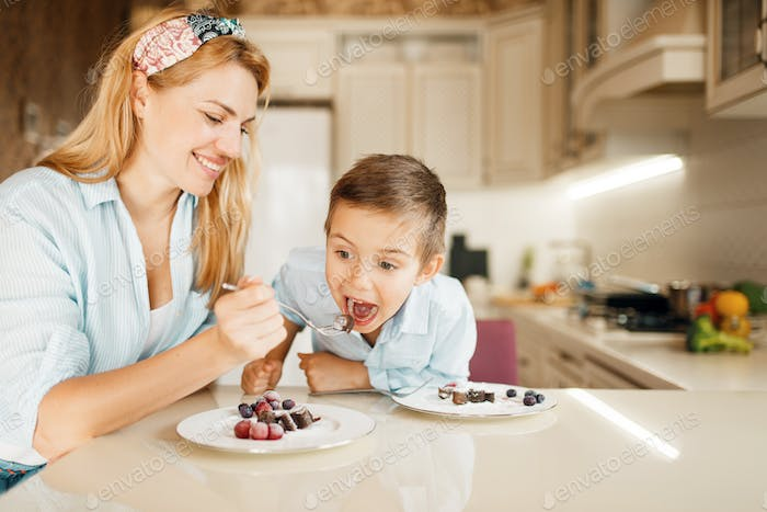 Mother with kid tasting dessert and having fun