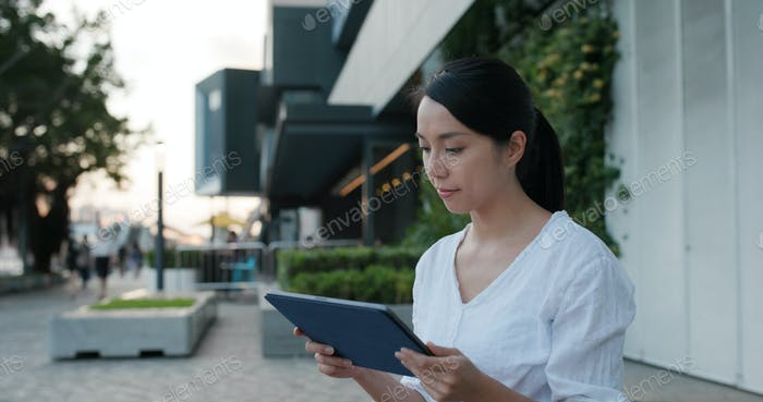 Woman use of tablet computer in city
