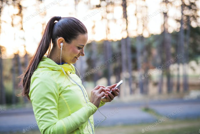 A young female runner outdoors in autumn nature, using smartphone.