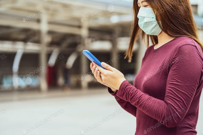 Closeup Asian woman hand using smart mobile phone with safety medical face mask