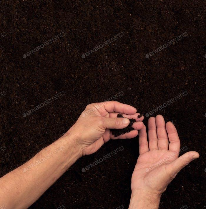 Farmer hands checking the soil on dark background