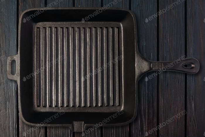 Empty frying pan on wooden background