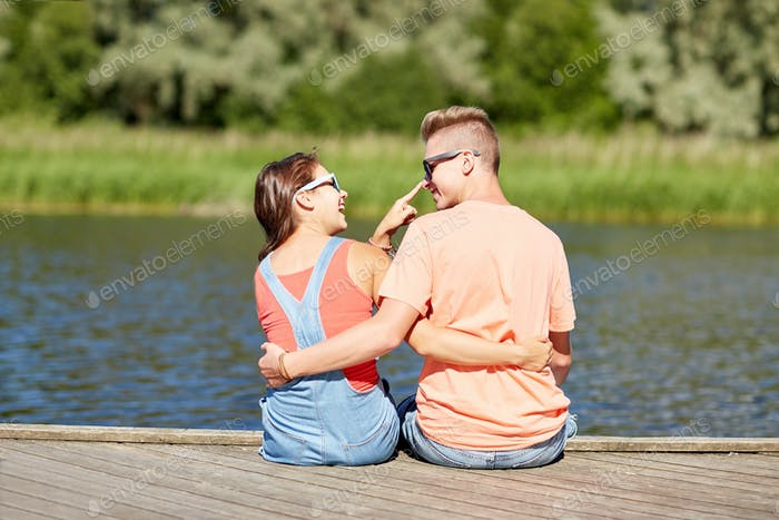 happy teenage couple hugging on river summer berth