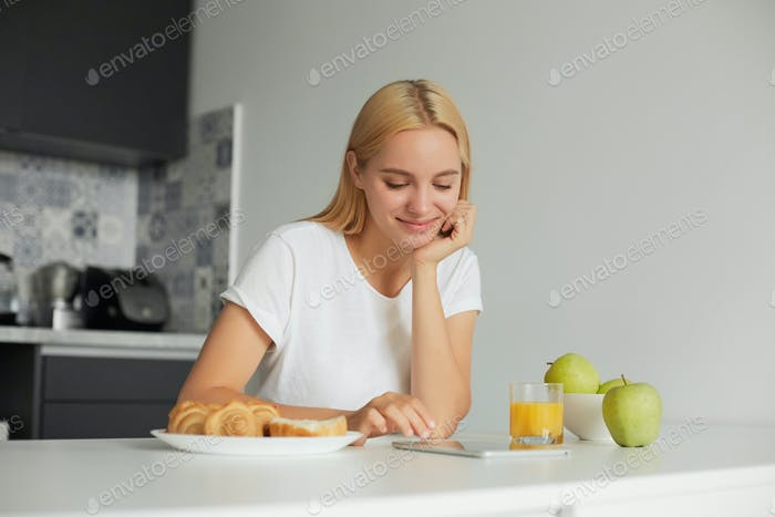 Woman sits at the kitchen table in the morning, smiling, looks at tablet black screen