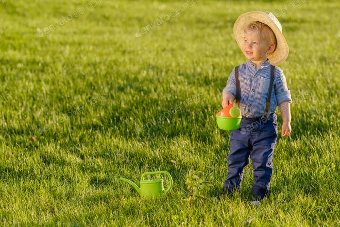 Thumbnail for Toddler child outdoors. One year old baby boy wearing straw hat using watering can