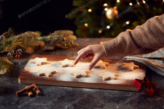 Womans Hand Reaches For Freshly Baked Star Shaped Christmas Cookies On Board Dusted With Icing Sugar