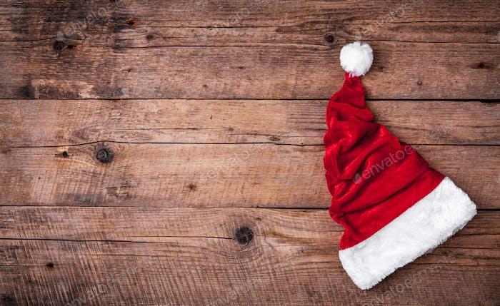 Weihnachtsmann roter Hut auf Holzhintergrund, Feiertag Weihnachten