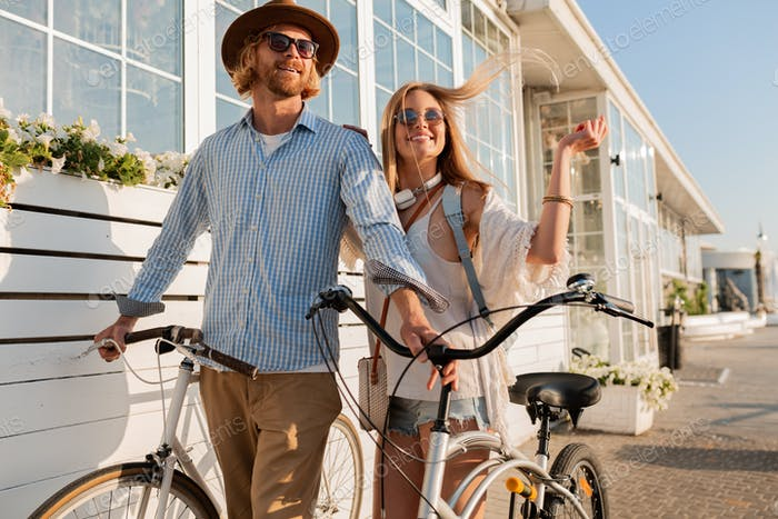 attractive happy couple of friends traveling in summer on bicycles