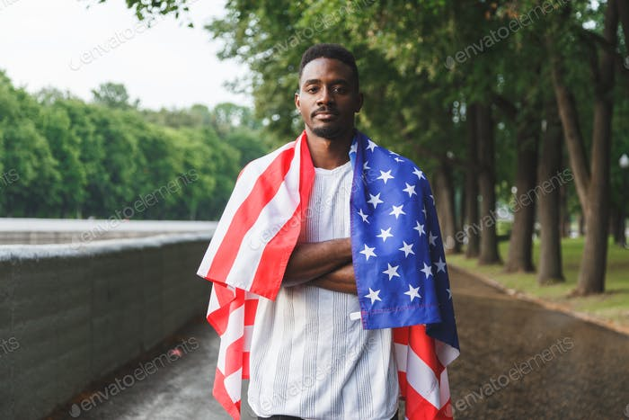 Afro American man with USA flag on his shoulders looking at camera, standing outdoors. Day summer