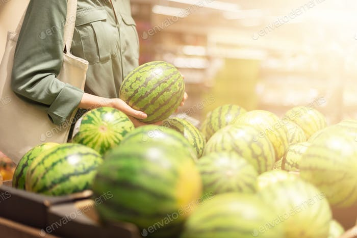 Woman choosing watermelon in market. Zero waste, plastic free concept. Sustainable lifestyle