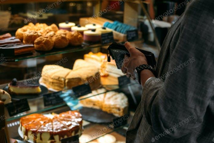 Cliente de confitería, cliente en tienda de dulces, pastelería. Vista posterior de la mujer joven elegir la torta