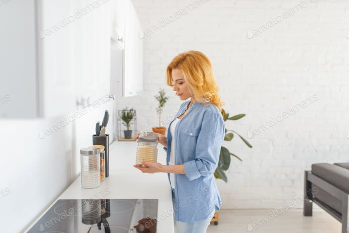 Woman prepares to cook breakfast on the kitchen