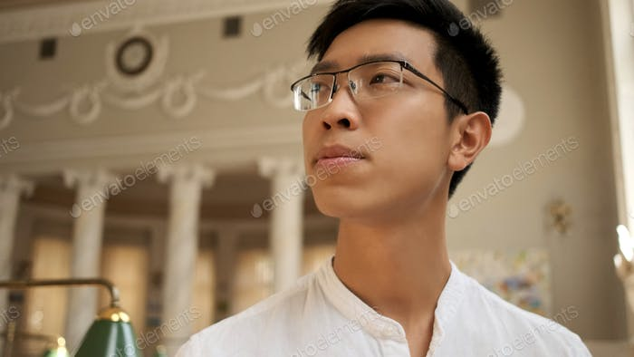 Attractive asian male student in eyeglasses thoughtfully looking away studying in university