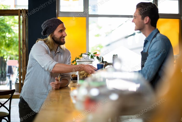 Smiling waiter serving cup of coffee to man at counter