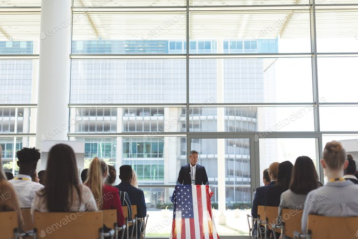 Front view of mixed race businessman speaking in a business seminar in office building