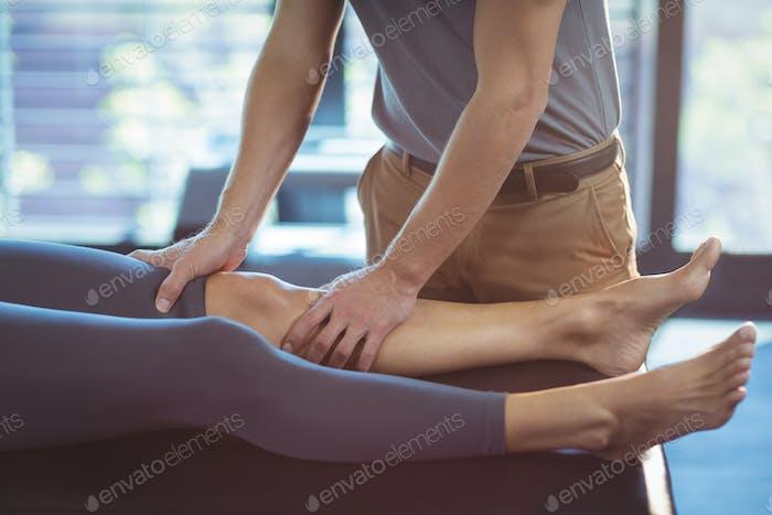 Physiotherapeut, die einer Frau eine Knietherapie schenkt