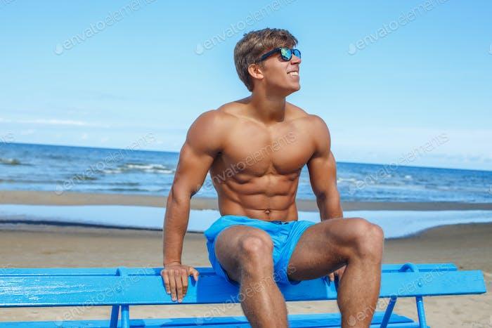 Shirtless muscular man in sunglasses.