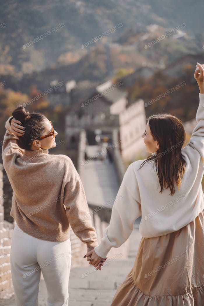 two female friends walking along the Great Wall of China near the Beijing entarnce