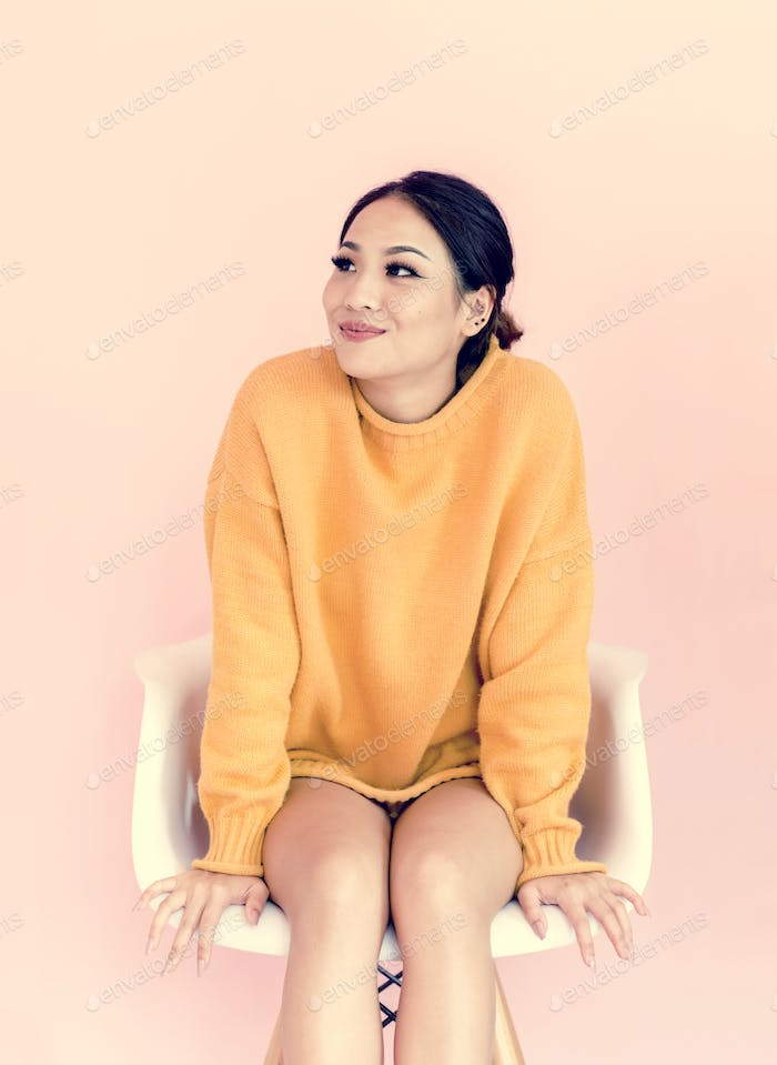 Asian woman sitting on white chair with pink background
