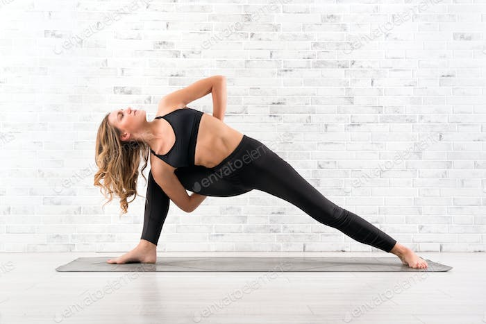 Fit woman doing utthita parsvakonasana yoga pose