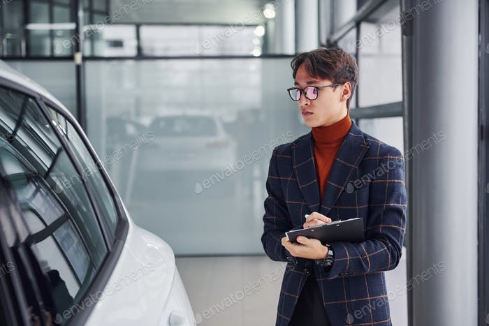 Worker in formal wear with notepad looking at modern car