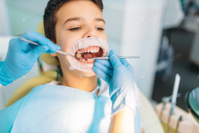 Boy in a dental cabinet, caries removal
