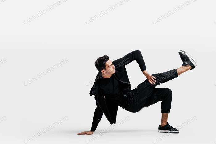 Handsome young man wearing a black sweatshirt and black pants is dancing breakdance doing dancing