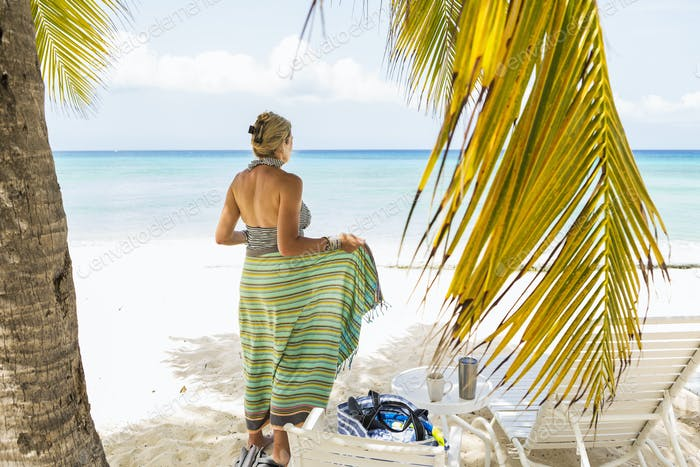 adult woman wrapping herself in a colorful sarong at the beach