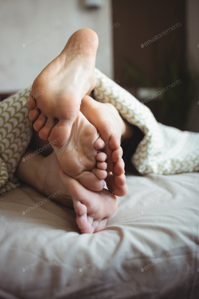 Couple showing their feet while lying on a bed