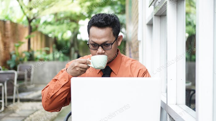 entrepreneurs working at computers  drinking coffee and smiling