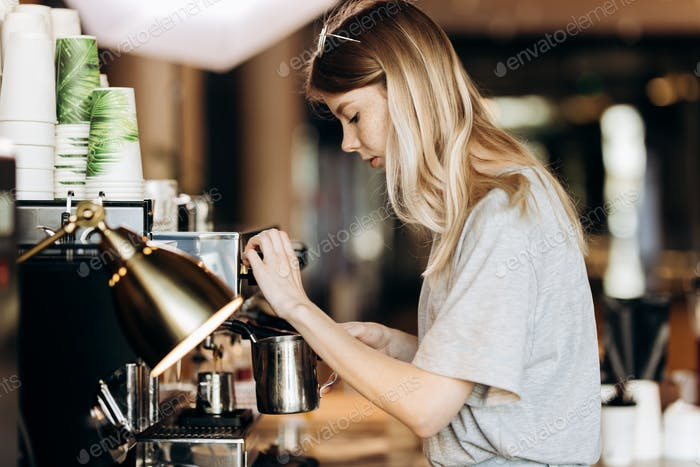 A youthful pretty thin blonde with long hair,dressed in casual outfit,is cooking coffee in a modern