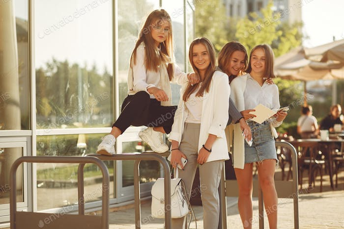 Four students on a student campus with a notebooks