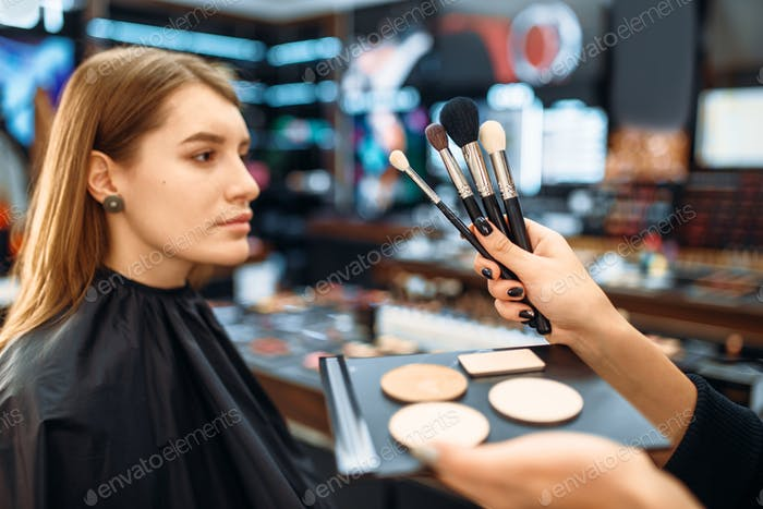 Visagiste hand with brushes against customers face